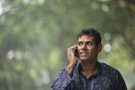 kurta: Happy Indian man using a smart phone on street. Traditional indian male wearing a kurta with smart phone outside. Stock Photo