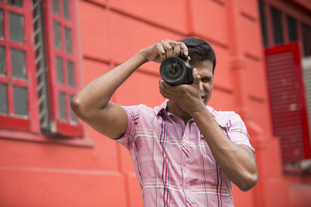 outside shooting: Portrait of happy Indian man taking photos with a camera in the city. Asian Photographer shooting outside with digital camera.