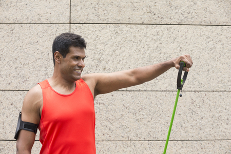 stretch: Portrait of an athletic Indian man using stretch bands outdoors in urban setting. Stock Photo