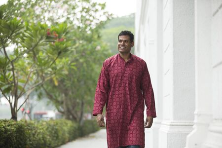 kurta: Happy indian man walking outdoors. Portrait of an indian man wearing a Traditional kurta walking.