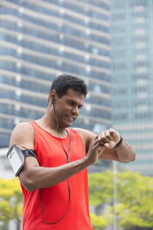 armband: Sporty Indian man looking at his smartwatch heart rate monitor. Athletic Asian man using a smart watch and listening to music with earphones. Stock Photo