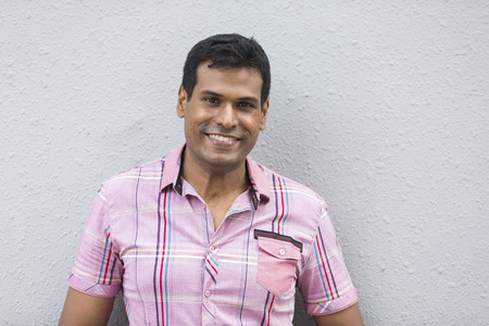 Indian man leaning on a grey wall. Handsome young Asian man leaning against a grey wall and looking at the camera