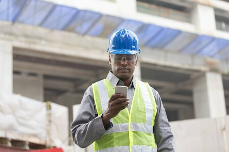 Portrait of a male Indian builder or industrial engineer at work using phone.
