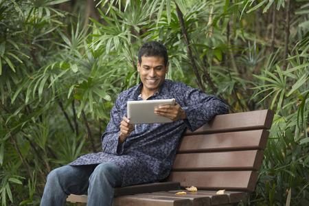 kurta: Happy Indian man using tablet computer on street. Traditional indian male wearing a kurta with tablet computer.
