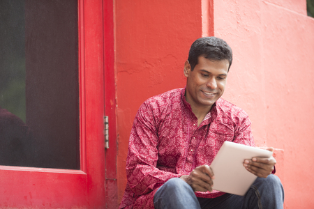 kurta: Happy Indian man using tablet computer on street. Traditional indian male wearing a kurta with tablet computer outside.