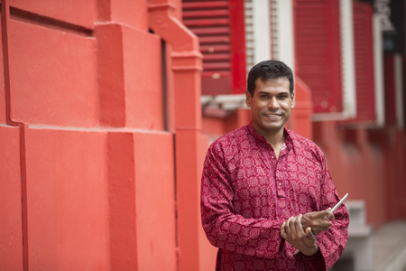kurta: happy indian man outdoors. Traditional indian male wearing a kurta with tablet computer. Stock Photo