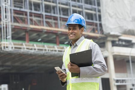 construction workers: Portrait of a male Indian builder or industrial engineer at work using phone.