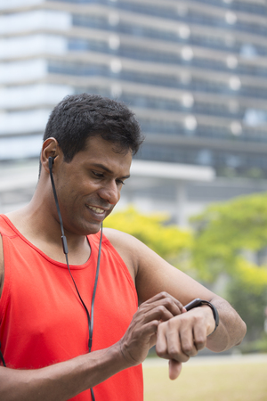 resting heart rate: Sporty Indian man looking at his smartwatch heart rate monitor. Athletic Asian man using a smart watch and listening to music with earphones. Stock Photo