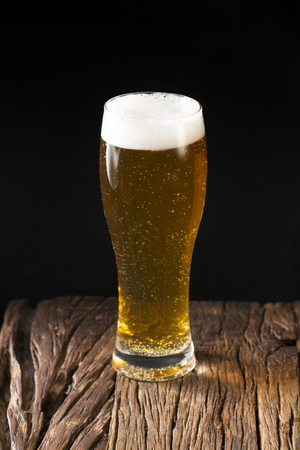A pint of Craft Beer sitting on a rustic wooden bar. Handcrafted microbrewery ale.