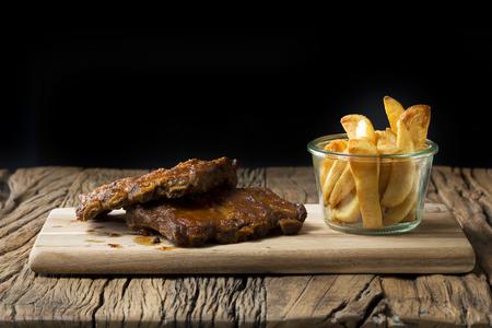 Côtes de porc BBQ et frites assis sur une table en bois rustique.