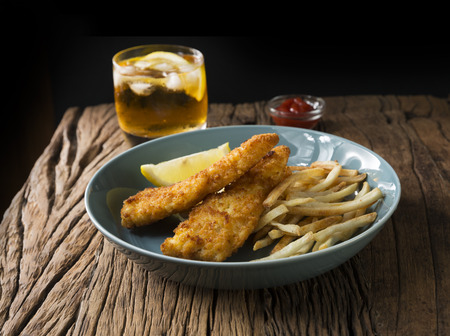 uk cuisine: Freshly cooked fish and chips on a rustic wooden background. Gastropub style food. Stock Photo