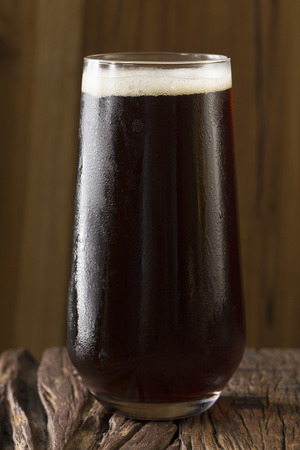 microbrewery: A pint of Craft Beer sitting on a rustic wooden bar. Microbrewery porter.