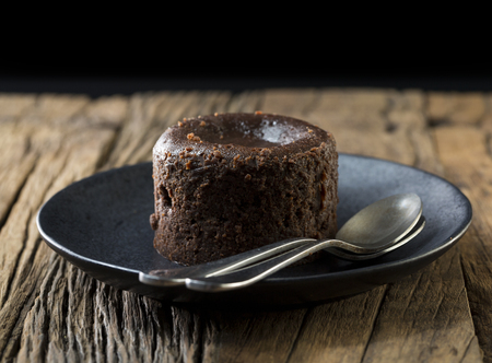 chocolate pudding: Homemade Chocolate Lava Cake. Chocolate pudding sitting on a rustic wooden table.