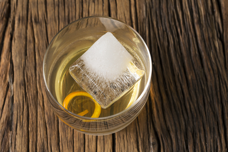 cocktail bar: Glass of Scotch whisky on an old rustic wooden background. Modern styling with one large ice cube and orange peel as a garnish. Stock Photo