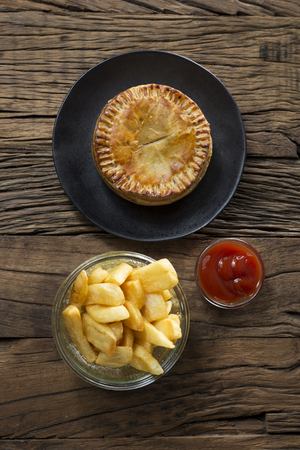 uk cuisine: A Traditional British meat pie and chips sitting on a rustic wooden table.