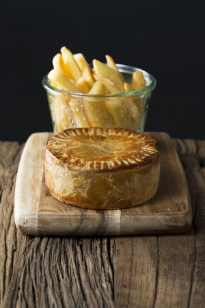meat pie: A Traditional British meat pie and chips sitting on a rustic wooden table.