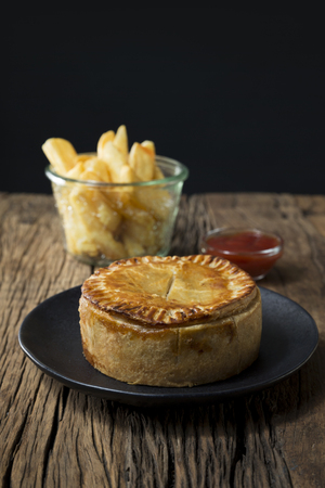 british food: A Traditional British meat pie and chips sitting on a rustic wooden table.