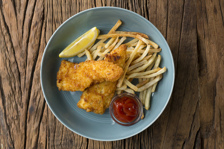 uk cuisine: Freshly cooked fish and chips on a rustic wooden background. Gastropub style food. View from above.