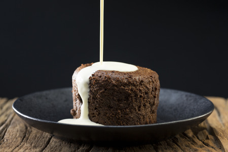 Fresh cream being poured over a Chocolate Lava Cake. Chocolate pudding sitting on a rustic wooden table. Stock Photo