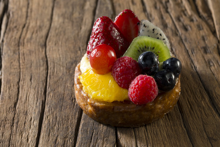 flan: Fresh Fruit Flan sitting on a rustic wooden table.