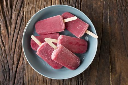 paletas de hielo: Caseras frambuesa y vainilla de hielo hace estallar en un fondo de madera rústica. pops helado Berry. El alimento del verano.