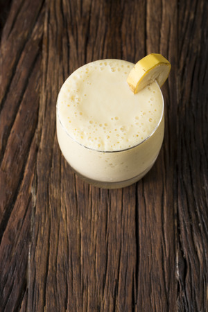 bannana: A Glass of fresh mango or bannana fruit smoothie, on a rustic wooden background.