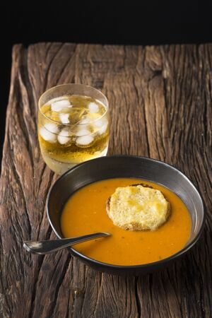 rustic food: Tomato soup on a wooden table. Rustic and wholesome food.