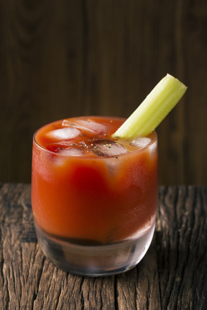 bloody mary cocktail: A bloody mary cocktail sitting on a rustic wooden bar.