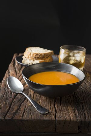 wholesome: Tomato soup on a wooden table. Rustic and wholesome food.