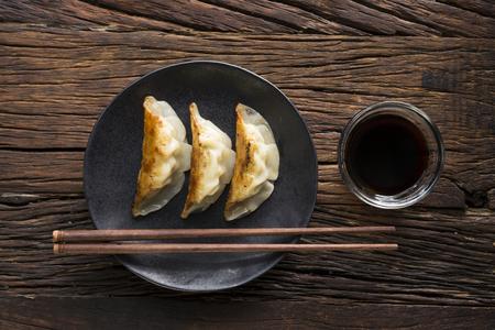 gyoza: A plate of Japanese gyoza dumplings sitting on a rustic wooden table. Stock Photo