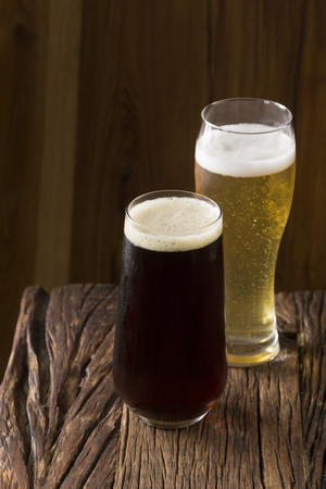 Two pints of Craft Beer sitting on a rustic wooden bar. Handcrafted microbrewery ale and porter. Stock Photo