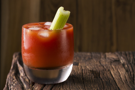 tomato cocktail: A bloody mary cocktail sitting on a rustic wooden bar.