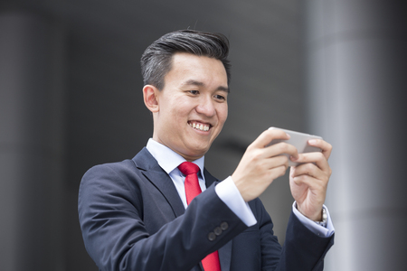 asian business man: Chinese business Man using his Smart phone outdoors in Asian city. Stock Photo