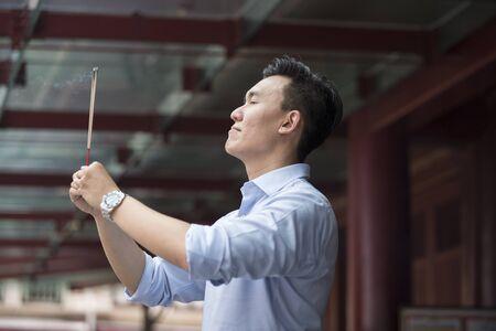 incienso: Un hombre de negocios chino está orando en un templo budista y la quema de incienso. Hombre asiático orando en un templo.
