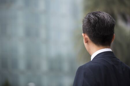 asian business man: Rear view of an Asian businessman looking away. Chinese business man standing outdoors.