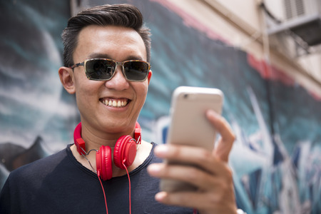 stylish men: Portrait of a trendy Chinese man leaning against a wall using his smart phone.