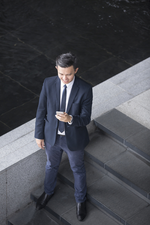 elevated: Elevated view of an Asian businessman using his Smart phone.