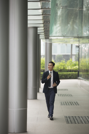 casual men: Portrait of a confident asian businessman walking in the city. Stock Photo
