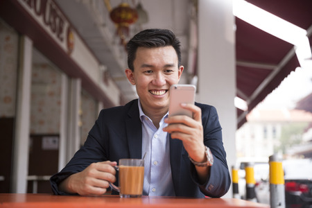 Chinese business man drinking a cup of coffee while sitting with his phone in an Asian food court or Hawker centre cafe. Stock Photo - 57344736