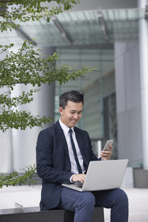 out of doors: Chinese business Man using his laptop out doors in modern city. Business on the move concept. Stock Photo