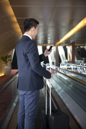 business traveller: Chinese business Man using his Smart phone on a moving walkwaytravelator. Asian business traveller.