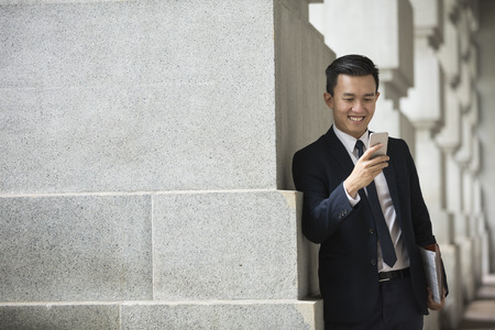 Chinese business Man using his Smart phone outdoors in Asian city. Stock Photo