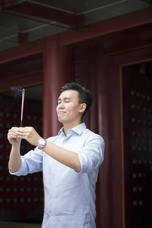 chinese courtyard: A Chinese businessman is praying at a Buddhist temple and burning incense. Asian man praying in a temple.