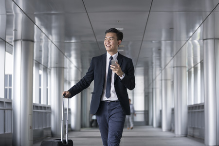 Portrait of a confident asian businessman walking in the city. Banco de Imagens
