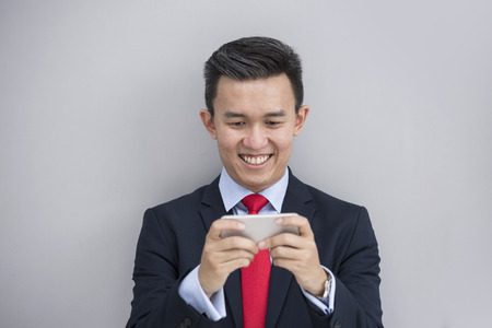 happy asian people: Chinese business Man using his Smart phone outdoors in Asian city. Stock Photo