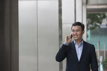 happy worker: Chinese business Man using his Smart phone outdoors in Asian city. Stock Photo