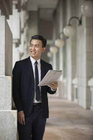 taking a break: Chinese Business man Outside Office reading a newspaper. Asian business man taking a break. Stock Photo