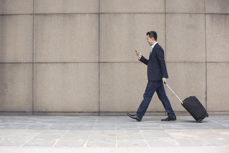 business man phone: Portrait of a confident asian businessman walking in the city. Stock Photo