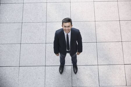 angle: High angle view of a happy Asian businessman looking at the camera. Stock Photo