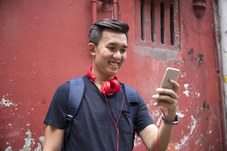 using phone: Portrait of a trendy Chinese man leaning against a wall using his smart phone.